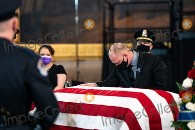 Photo - United States Capitol Police officer Ken Shaver who was also injured in the April 2nd car attack at the Capitol center pays his respects to the late US Capitol Police officer William Billy Evans as he lies in honor in the Rotunda of the US Capitol in Washington DC on April 13th 2020Credit Anna Moneymaker  Pool via CNPAdMedia