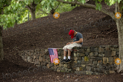 Photo - A child wearing a Trump hat sits in front of Trump National Golf Club in Sterling Virginia on Sunday August 2 2020 as United States President Donald J Trump prepares to go back to the White House in Washington DC US  Credit Stefani Reynolds  CNPAdMedia