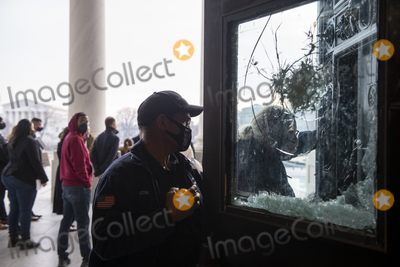 Photo - Men work on repairing the shattered windows of the door to the entrance of the US Capitol as preparations are made for the upcoming inauguration of President Joe Biden at the US Capitol in Washington DC Friday January 15 2021 Credit Rod Lamkey  CNPAdMedia