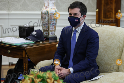 Photos From Pete Buttigieg wears a protective mask while speaking during a meeting on infrastructure with House members in the Oval Office of the White House in Washington