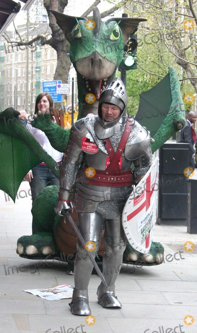 Sable Photo - London UK Lloyd Scott MBE a former firefighter a former professional football player and self-described mad charity fundraiser pictured here on his latest charity fund raiser attempting to complete the 2006 London Marathon which fell on St Georges Day dressed as the knight himself in a suit of armour and pulling a dragon behind him The suit of armour and the dragon weigh approximately 300lbs He is also attempting to get into  the Guinness Book of World Records by being the first to raise 1million as an INDIVIDUAL fundraiser After surviving leukaemia he has raised more than 4 million for cancer charities such as Children with Leukemia through what he calls extreme charity fundraising events including the followingthe Flora London Marathon wearing a 110 lb deep-sea diving costume in 2002 setting a world record for the slowest marathon time again wearing a deep-sea diving suit at the Edinburgh Marathon with a time of six days four hours 30 minutes and 56 seconds the first underwater marathon walking a 26 mile stretch of the bottom of Loch Ness Scotland in 2003 the Lands End to John OGroats swim in 2004 where he swam from John OGroats to Lands End in a water tank on the back of a lorry Everest Marathon in 2004 135 mile Death Valley Ultra marathon in 2004 Marathon des Sables in 2004 Walked to the North Pole in 2004 and Walked to the South Pole in 2004 After being awarded an MBE in 2005 Scott joked that the award should stand for Mad Bonkers  Eccentric He recently visited Australia where he travelled 2700 miles from Perth to Sydney on a penny farthing while dressed as Sherlock Holmes (including deerstalker hat tweed jacket and fake moustache)26 April 2006Georgie BelcherLandmark Media